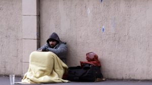 A man sits on the ground and begs for money on December 26, 2012 in Paris. AFP PHOTO / JOEL SAGET